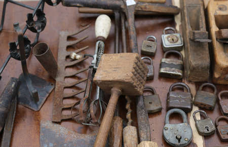 flea market: wooden hammer and rusty padlocks and planers in the workshop of flea market