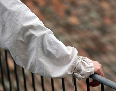 hand rail: Nobles hand with the ancient dress resting on the railing of the medieval castle