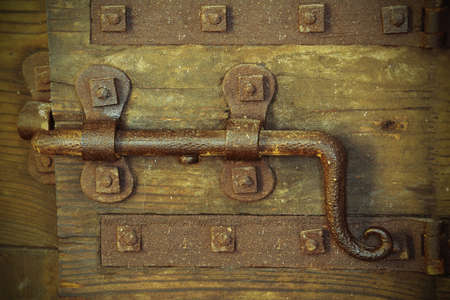 old rusty lock with ig deadbolt to close the door of the medieval castle photo