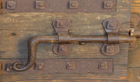 old lock with deadbolt to close the door of the medieval castle photo