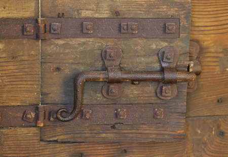 old rusty lock with big deadbolt to close the door of the castle photo