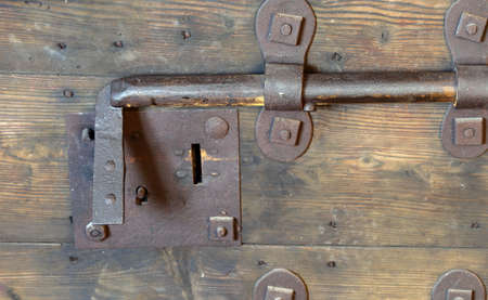 deadbolt: old rusty lock with big deadbolt to close the door of the castle Stock Photo
