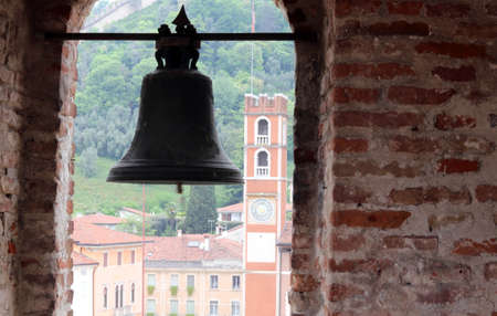 historical periods: ancient bronze Bell of the Castle and the old tower in piazza degli scacchi in Marostica in Northern Italy