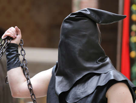 executioner with black hood on his head and the chain with the sentenced to death Stock Photo