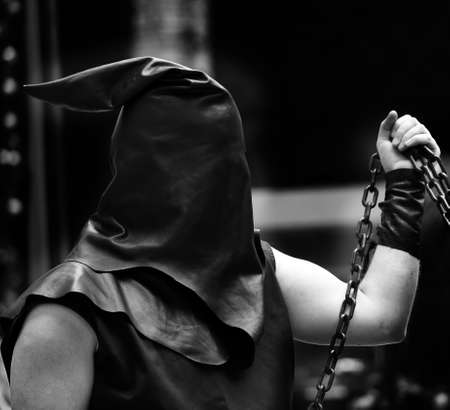 sentenced: executioner with black hood on his head and the chain with the sentenced to death Stock Photo