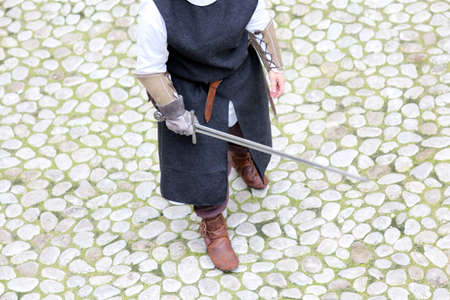 a war historian: ancient medieval soldier with sword during the final duel Stock Photo