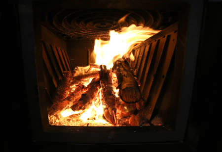 stove fire: inside of stove with fire and glowing embers Stock Photo