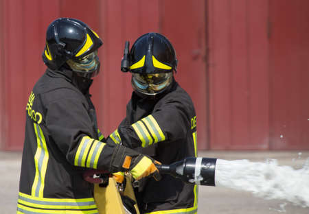 fireman: two firemen in action with foam to put out the fire