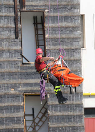 rappel: fearless fireman during an exercise carries the stretcher with the climbing rope Stock Photo