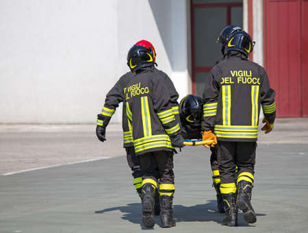 fellow: Four brave Firefighters carry a fellow firefighter with the medical stretcher Stock Photo