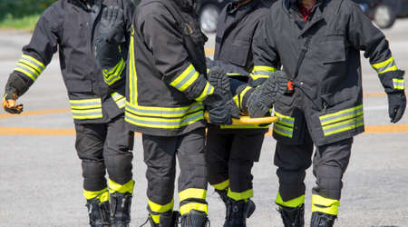 Four brave Firefighters carry a firefighter with the medical stretcher