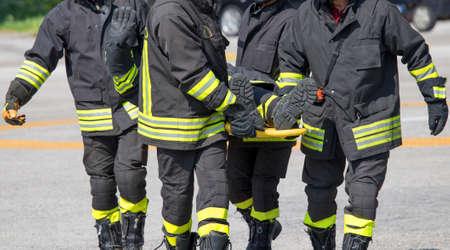 bombero: Cuatro valientes bomberos llevan un bombero con la camilla m�dica Foto de archivo