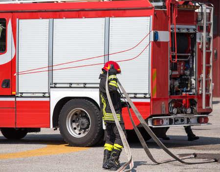 voiture de pompiers: pompiers avec le tuyau pour �teindre les incendies et le grand camion de pompier