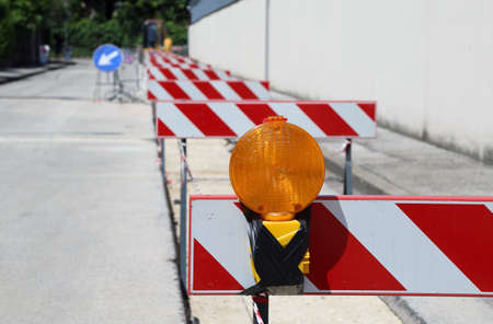 roadwork: Orange lamp in roadworks and protection stands above the excavation Stock Photo