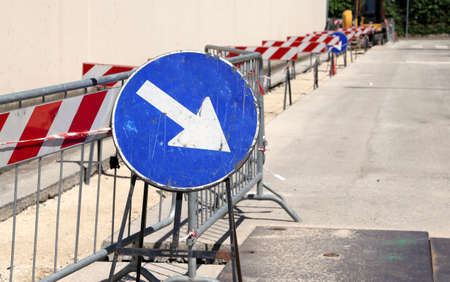 big road signal with arrow on the excavation during the roadworks for the laying of cables