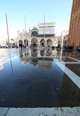 procuratie: VENICE, VE, ITALY - January 31, 2015: Saint Marks Basilica during high tide  with tourists and water in st. marks square Editorial