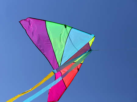 tethered: great kite flying high in the sky blue