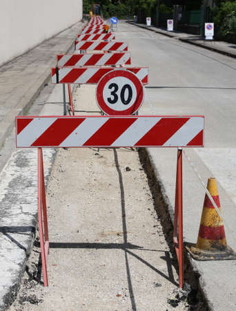 roadwork: speed limit sign and many hurdles in the road excavation