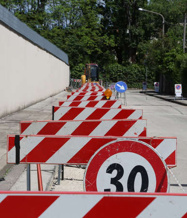 roadwork: speed limit sign and hurdles in the road excavation for the laying of optical fibre
