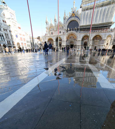 saint mark's square: VENICE, VE, ITALY - January 31, 2015: Saint Marks Basilica during high tide  with tourists and water in st. marks square Editorial