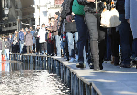 ve: VENICE, VE, ITALY - January 31, 2015: tourists in Venice walk on the raised sidewalk at high tide in St. Marks square