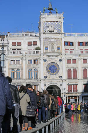 clock of the moors: VENICE, VE, ITALY - January 31, 2015: tourists in Venice walk on the raised sidewalk at high tide in St. Marks square