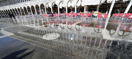 procuratie: VENICE, VE, ITALY - January 31, 2015:bar tables and the palazzo delle Procuratie Nuove in Venice during high tide with St. Marks square under water