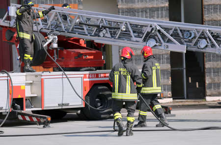 engine fire: firefighters during an emergency with protective suits and helmets Stock Photo