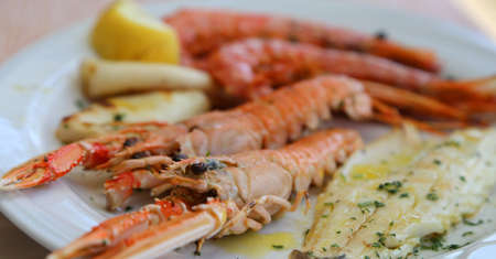 langoustine: grilled fish with sea bream prawns and shrimps at the restaurant Stock Photo