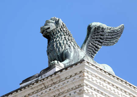 leon con alas: estatua del león alado de San marca con su pata sobre el libro Foto de archivo