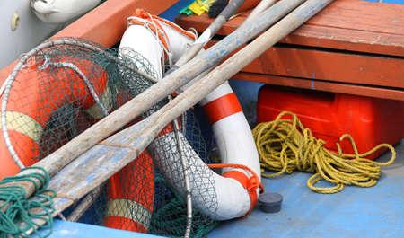 redes de pesca: aros salvavidas y remos redes de pesca en un barco amarrado en el muelle Foto de archivo