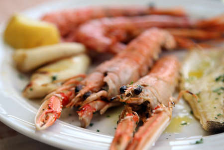 norvegicus: two large prawns grilled in the dish of the restaurant Stock Photo