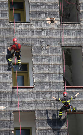 workouts: rescuers during the workouts climbing the facade of a building Stock Photo