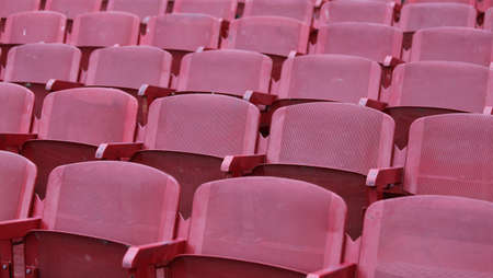 absenteeism: red empty chairs in the stadium before the concert Stock Photo