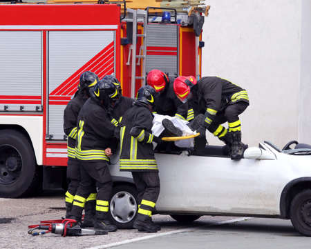 relieve: brave firefighters relieve an injured after car accident Stock Photo