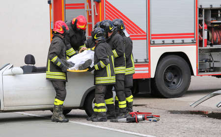 italian car: brave firefighters relieve an injured after car accident Stock Photo