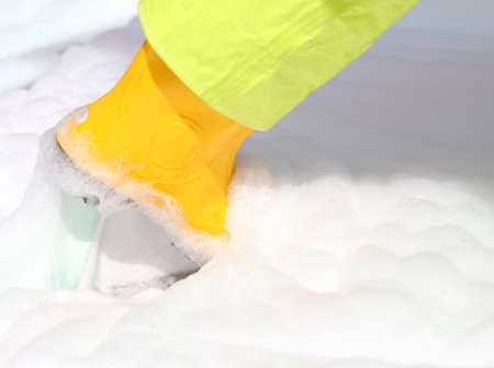 remediation: Yellow boots into the foam pollutant during the work of environmental remediation
