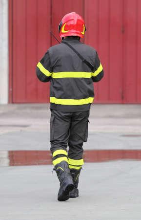 casco rojo: Bomberos en el uniforme con el casco rojo en la estación de bomberos