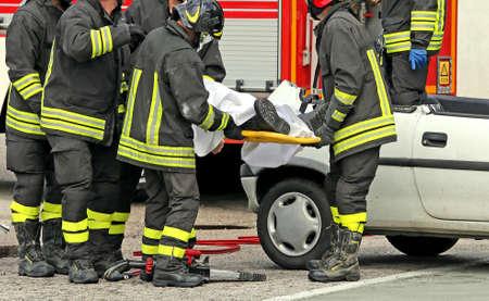 bombera: herido realizado por los bomberos en una camilla después del accidente de tráfico