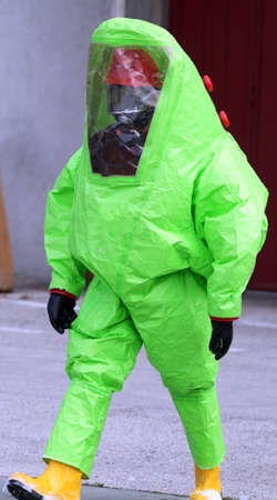 chemical warfare: man with green protective suitagainst biological risk