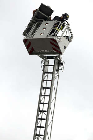 PUMPER: firefighters in the fire truck basket during the practice of training in firehouse Stock Photo