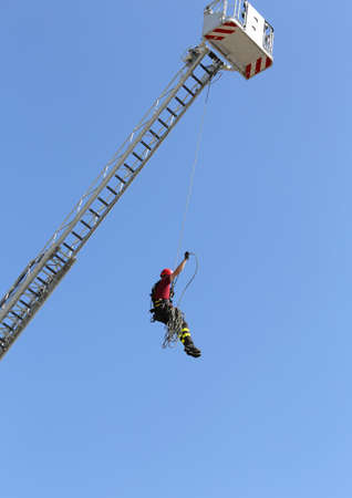 rappel: climber firefighters hung the rope climbing during the practical exercise in firehouse