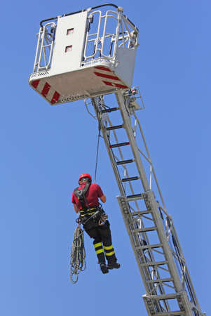 rappel: expert fireman hung the rope climbing during the practical exercise in firehouse