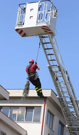 rescuer: expert firefighter down with the rope in the building during a fire alarm