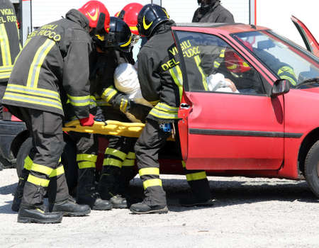 rescuer: firefighters in action and pull the injured from the car