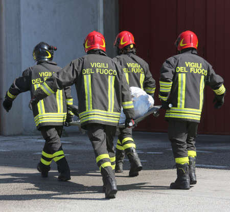 rescuer: four firefighters in action carry a stretcher with injured
