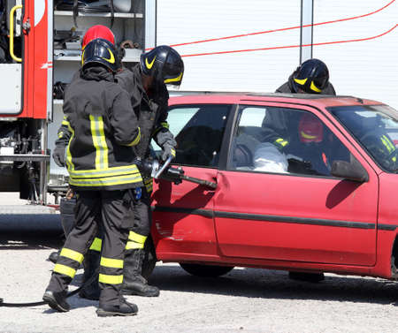pneumatic: Firefighter opens car door with pneumatic shears after the traffic accident