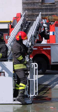 voiture de pompiers: pompier dans la cage du moteur de feu