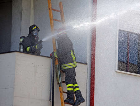 fire station: Firefighter sprays water with the spear fighting during the exercise in the fire station