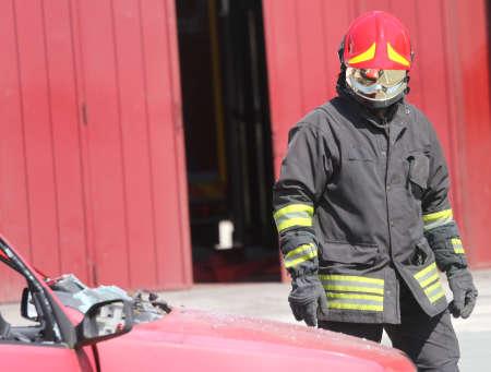 casco rojo: aislado bombero italiano con uniforme de protección y casco rojo en la cabeza